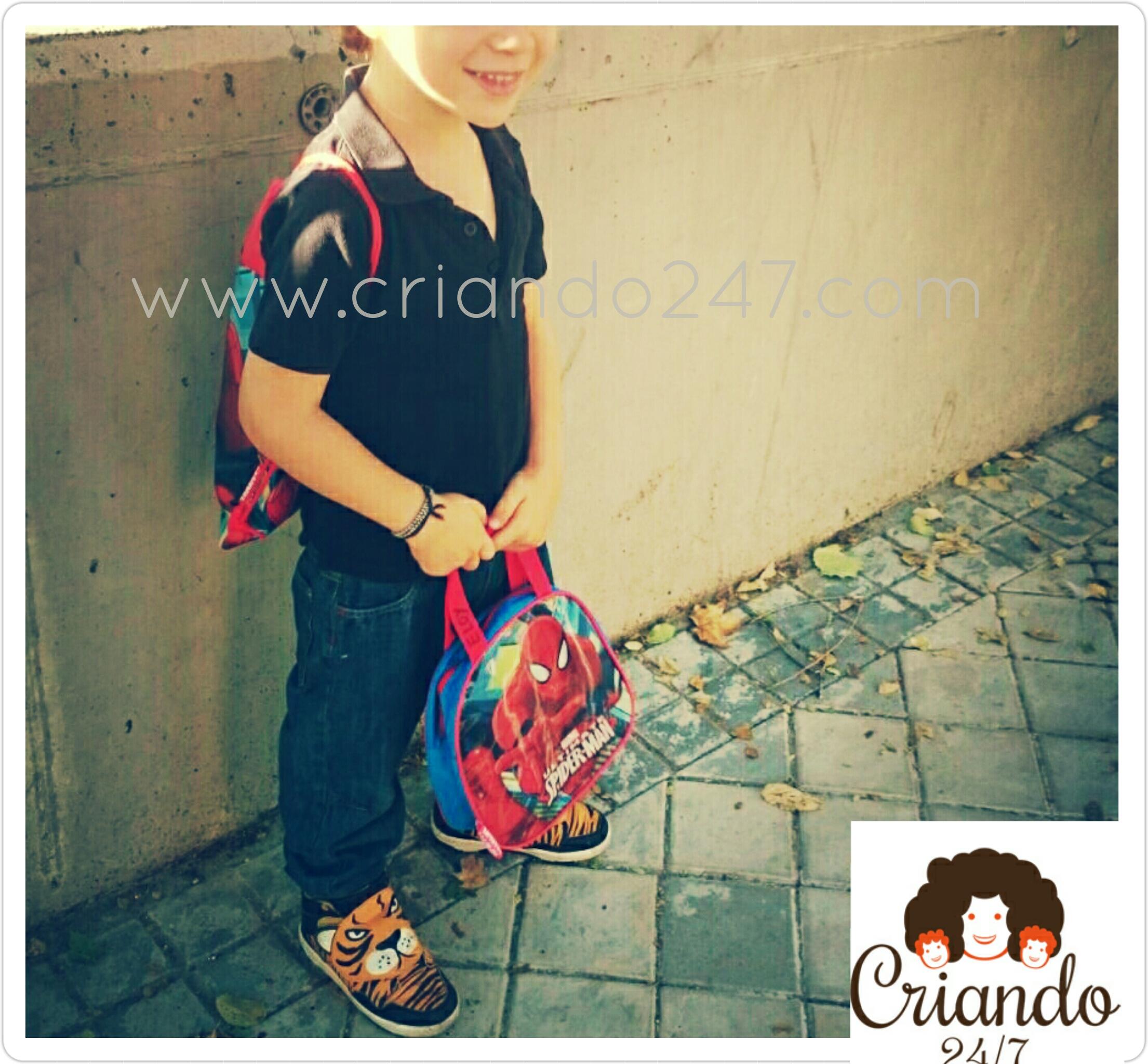 mi hijo sonriendo, de pie, con una mochila colgada en la espalda y una bolsa de merienda en las manos.