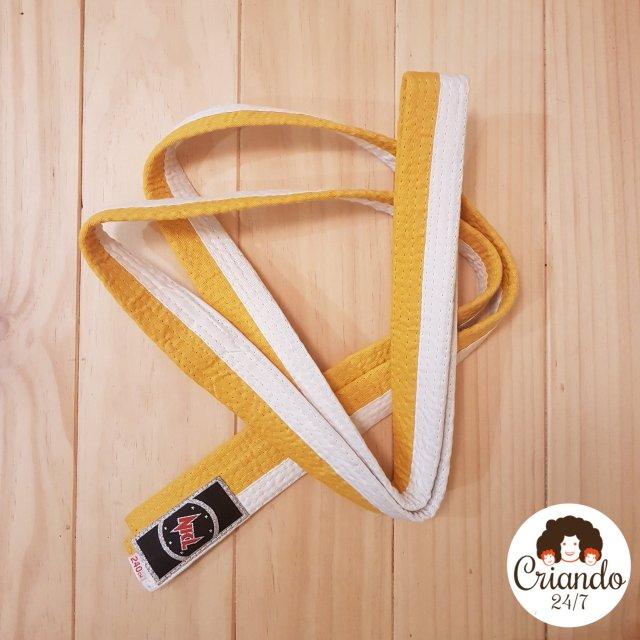 cinto de judo bicolor amarillo y blanco, dblado sobre una mesa de pino y logo de criando 24/7