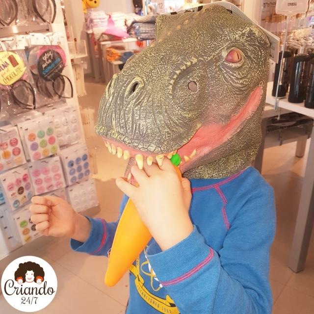 Primer plano de un niño con una máscara de dinosaurio, sosteniendo una zanahoria de juguete como si fuese a comérsela. Logo de Criando 24/7